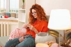 Flickan som bär exponeringsglas som sitter på soffan med stort handarbete, clews royaltyfri foto