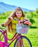 Flickan som bär röda prickar, klär ritter cyklar in i parkerar Arkivfoto