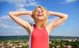 Flickan som behas med varmt solljus, ser avkopplad bakgrund för blå himmel Ta omsorghudarmhålan Blont avslappnande för kvinna uto arkivfoto
