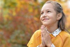 Flickan som ber i höstligt, parkerar Arkivfoto