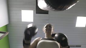 Flickan som boxaren slår en boxas påse, kameran, skjuter från den lägre vinkeln stock video