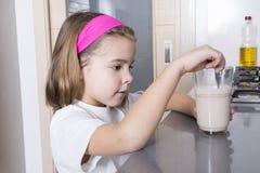 Flickan som förbereder ett exponeringsglas av, mjölkar Royaltyfri Foto