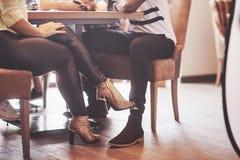 Flickan som flörtar med en rörande grabb, lägger benen på ryggen hennes fot under tabellen i ett kafé, medan ha gyckel med vänner Arkivfoton