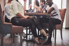 Flickan som flörtar med en rörande grabb, lägger benen på ryggen hennes fot under tabellen i ett kafé, medan ha gyckel med vänner Royaltyfri Bild