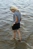 Flickan som går i, blir grund av floden Royaltyfria Bilder