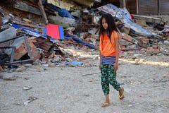 Flickan som går passerandet, kollapsade byggnad efter jordskalvkatastrof Fotografering för Bildbyråer