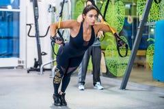 Flickan som gör övningar med trx på idrottshallen, skjuter ups livsstil för kondition för begreppssportgenomkörare sund Fotografering för Bildbyråer