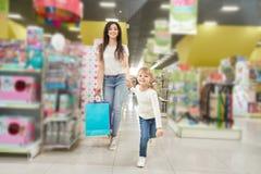 Flickan som h?ller handen av modern och fram?triktat k?r shoppar in royaltyfri fotografi