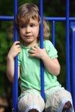 flickan som håller skyddsstänger, sitter Royaltyfri Fotografi