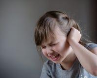 Flickan som har örat, smärtar att trycka på hans smärtsamma huvud som isoleras på grå bakgrund arkivfoton