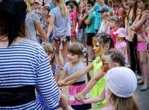 Flickan som iklädd piratkopierar dräkten, leder roundelay med gruppen av barn arkivfoto