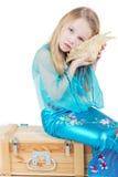 Flickan som kläs som mermaid, sitter och lyssnar för att stoja Royaltyfria Bilder