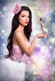 Flickan som kläs som en prinsessafe, rymmer i hans händer fantastisk brunettdocka på en färgrik bakgrund, Royaltyfri Fotografi