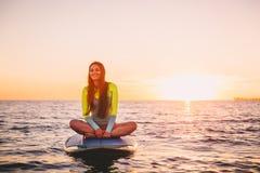 Flickan som kopplar av på, står upp skovelbrädet, på ett tyst hav med varma solnedgångfärger Royaltyfri Foto