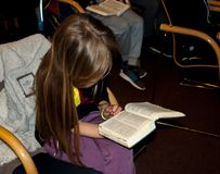 Flickan som läser bibeln på en kurs i barnens kristna läger royaltyfria foton