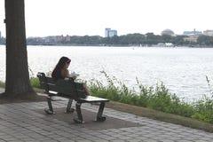 Flickan som läser en bok i, parkerar på bänken nära Charles River i Boston, Massachusetts royaltyfri foto
