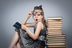 Flickan som läser en bok och, är mycket förvånad Royaltyfri Bild