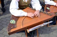 Flickan som leker med ethnographic, stränger musikal instrumenterar royaltyfri fotografi