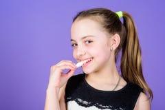 Flickan som ler framsidan, rymmer s?ta marshmallower i violett bakgrund f?r handen Gottegrisbegrepp Ungeflicka med l?nga h?rn?got royaltyfri bild