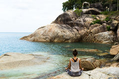 Flickan som mediterar på stenar vid havet, flickalånet med yoga ön Samui, yoga i Thailand Royaltyfri Bild