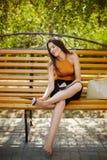 Flickan som ?r tr?tt av h?l, tar av hennes skor fr?n hennes fot och sitter p? parkerar barfota b?nken arkivfoto