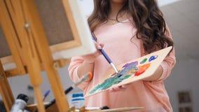 Flickan som rymmer en borste som blandar färgar för hennes bild stock video