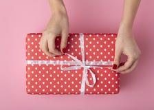 Flickan som rymmer en gåva i händer, kvinnors händer, öppnar asken som slås in i dekorativt papper på en pastellfärgad kulör rosa royaltyfria foton