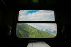 Flickan som ser fönstret av ett drev på denMostar drevlinjen, högväxta berg, är just nu synlig Arkivfoto