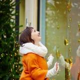 Flickan som ser parisiska skyltfönster, dekorerade för jul Arkivbild