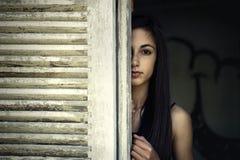 Flickan som ser till och med ett fönster, stänger med fönsterluckor Royaltyfri Foto