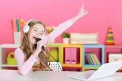 Flickan som sjunger in i en mikrofon Royaltyfria Foton