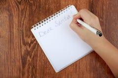Flickan som skrivar ett brev till Santa Claus på trätabellen royaltyfri fotografi