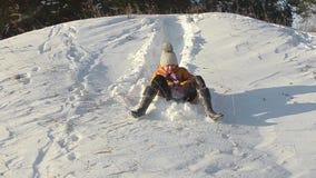 Flickan som sledding ner kullarna i en vinter, parkerar, tonåriga flickalekar med en hund i snön lager videofilmer