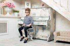 Flickan som spelar på pianot Arkivfoto
