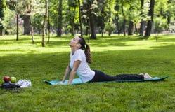 Flickan som sträcker i en gräsplan, parkerar Arkivfoton