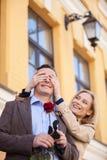 Flickan som täcker hennes pojkväns ögon, förvånade honom Arkivbild