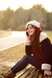 Flickan som talar på mobiltelefonen på bänk parkerar in Royaltyfria Bilder