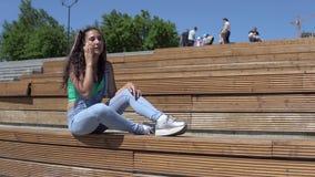 Flickan som talar på mobiltelefonsammanträde på bänk parkerar in 4K stock video