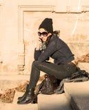 Flickan som talar på telefonen och sitter på trappa - värme filtret Arkivbild