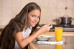 Flickan som äter sädesslag med, mjölkar att dricka orange fruktsaft för frukost Royaltyfri Bild
