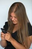 Flickan som texting med smart, ringer Arkivbilder