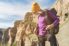 Flickan som turisten i solglasögon sätter en ryggsäck på naturen på en bakgrund av epos, vaggar att förbereda sig för trekking me fotografering för bildbyråer