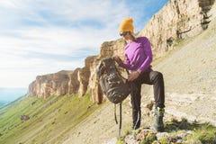 Flickan som turisten i solglasögon sätter en ryggsäck på naturen på en bakgrund av epos, vaggar att förbereda sig för trekking me royaltyfri bild