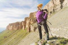 Flickan som turisten i solglasögon sätter en ryggsäck på naturen på en bakgrund av epos, vaggar att förbereda sig för trekking me arkivfoto