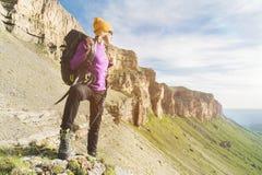 Flickan som turisten i solglasögon sätter en ryggsäck på naturen på en bakgrund av epos, vaggar att förbereda sig för trekking me arkivbilder