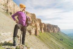 Flickan som turisten i solglasögon sätter en ryggsäck på naturen på en bakgrund av epos, vaggar att förbereda sig för trekking me royaltyfria bilder