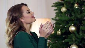 Flickan som tycker om te, kaffe, en kvinna, rymmer i handkopp av drinken, stående av en flicka som dricker teanseende nära lager videofilmer