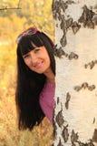 Flickan som ut ser på grund av en björk Royaltyfri Bild