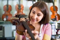 Flickan som väljer fiolen i musik, shoppar Royaltyfri Foto