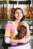 Flickan som väljer fiolen i musik, shoppar Arkivfoton